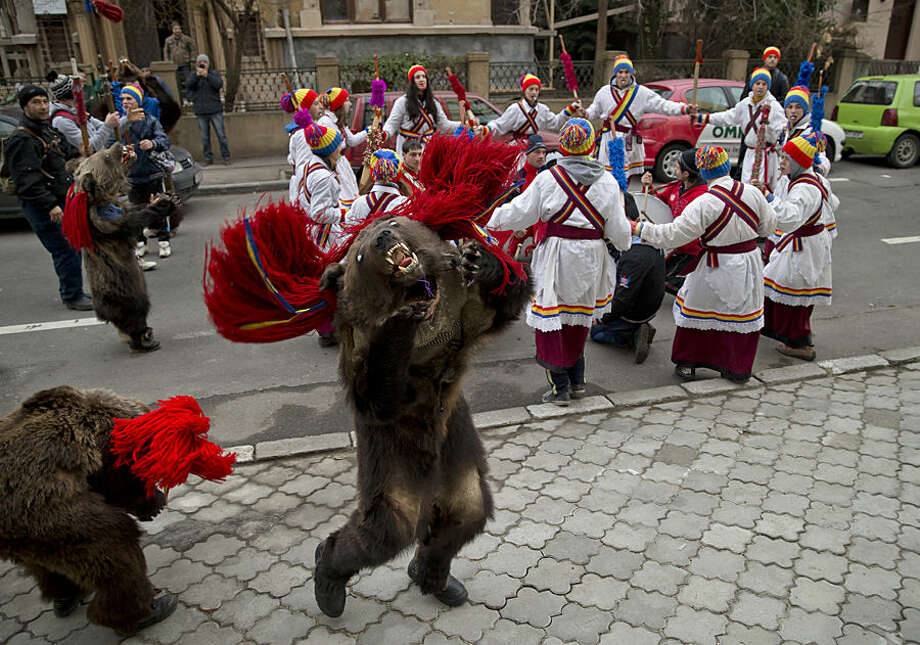 Children from Dofteana, northern Romania, some wearing bear furs, dance while performing a holiday season ritual in Bucharest, Romania, Tuesday, Dec. 23, 2014. In pre-Christian rural traditions, dancers wearing colored costumes or animal furs, touring house to house in villages singing and dancing to ward off evil. In recent years following the economic downturn in Romania, a European Union member since 2007, the tradition has moved to Romania's cities where dancers travel to perform the ritual for money during the Christmas and New Year's period. (AP Photo/Vadim Ghirda)