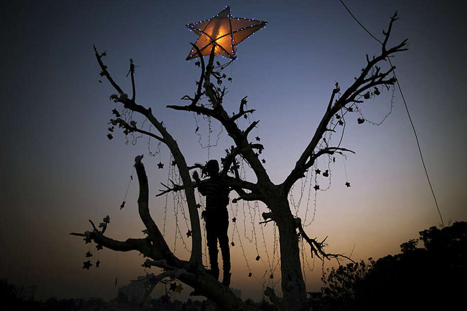 A Pakistani Christian boy decorates a tree in preparation for the upcoming Christmas holiday in Islamabad's slums, Pakistan, Tuesday, Dec. 23, 2014. (AP Photo/B.K. Bangash)