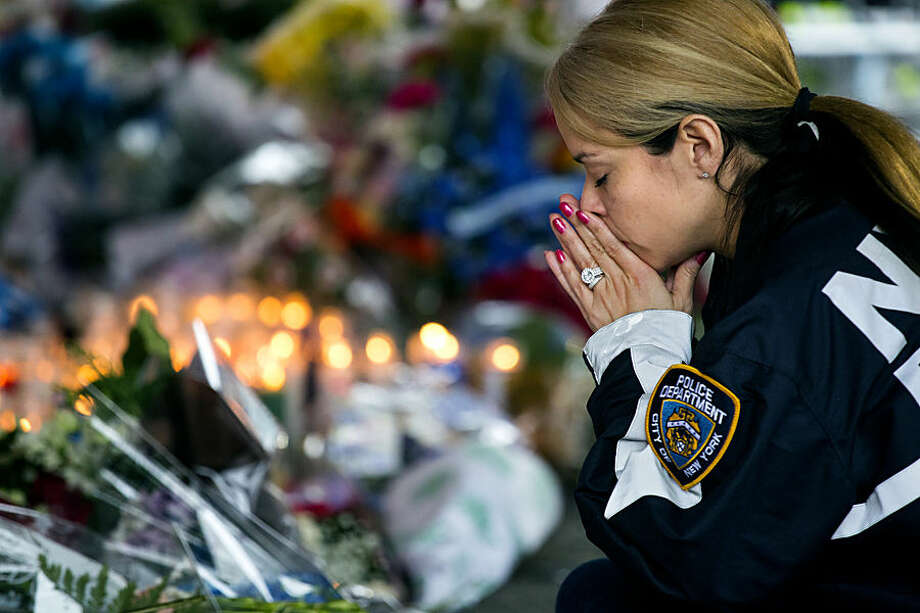 New York Police Department Lt. Tanisha Gurley visits a makeshift memorial, Tuesday, Dec. 23, 2014, near the site where NYPD officers Rafael Ramos and Wenjian Liu were murdered in the Brooklyn borough of New York. Police say Ismaaiyl Brinsley ambushed the two officers in their patrol car in broad daylight Saturday, fatally shooting them before killing himself inside a subway station. (AP Photo/Craig Ruttle)