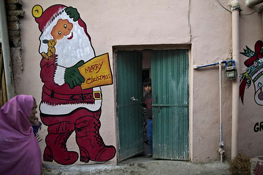 A Pakistani Christian woman, left, walks by a painting of a Santa Claus painted on a wall in preparation for Christmas holiday, in a Christian neighborhood in Islamabad, Pakistan, Tuesday, Dec. 23, 2014. (AP Photo/Muhammed Muheisen)
