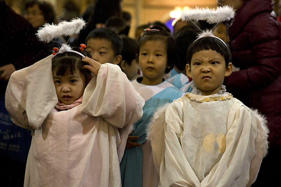 Children dressed as angels take part in a mass on the eve of Christmas at the South Cathedral official Catholic church in Beijing, China, Wednesday, Dec. 24, 2014. Estimates for the number of Christians in China range from the conservative official figure of 23 million to as many as 100 million by independent scholars, raising the possibility that Christians may rival in size the 85 million members of the ruling Communist Party. (AP Photo/Ng Han Guan)