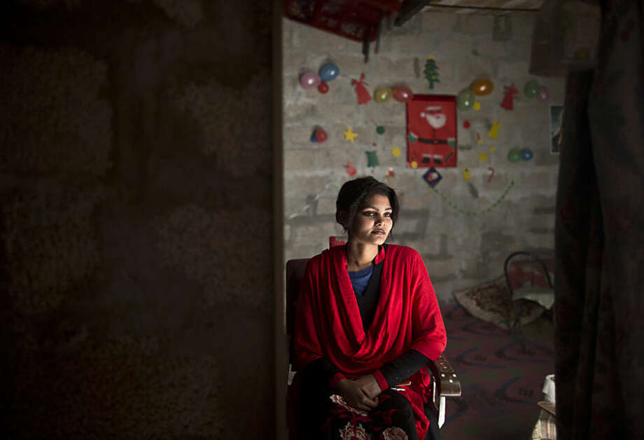 Pakistani Christian Maria Akbar, 15, checks herself in the mirror, after having her make up done by hairdresser Razia Rehmat, 39, in preparation for Christmas holiday, at a hair salon, in a slum that hosts Christian families, on the outskirts of Islamabad, Pakistan, Wednesday, Dec. 24, 2014. (AP Photo/Muhammed Muheisen)