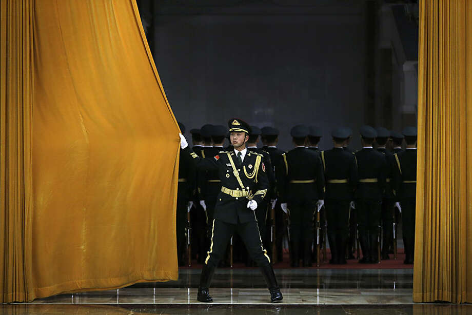 A Chinese People's Liberation Army soldier closes a curtain after members of honor guard rehearse for a welcome ceremony held by Chinese President Xi Jinping for visiting Egyptian President Abdel-Fattah el-Sissi at the Great Hall of the People in Beijing, China Tuesday, Dec. 23, 2014. (AP Photo/Andy Wong)