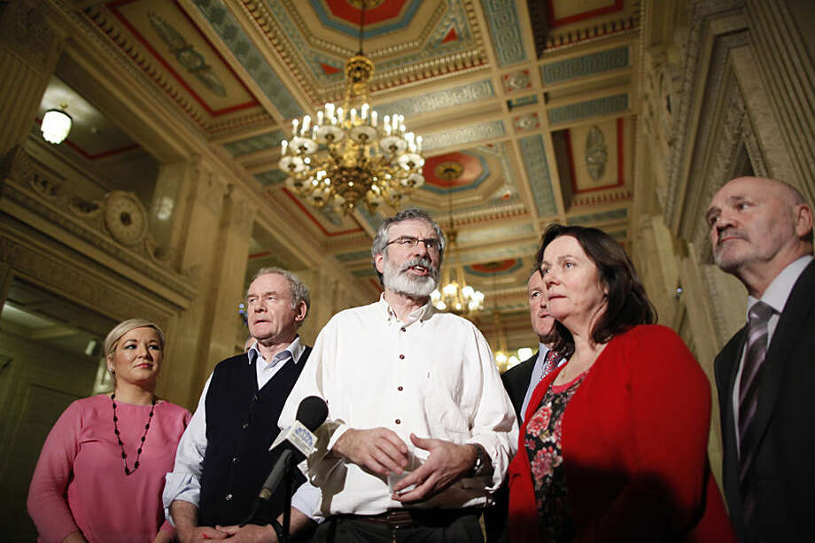 Sinn Fein President Gerry Adams, centre, and party members Michelle O'Neill, left, Martin McGuinness, 2nd left, Conor Murphy, 3rd right, Jennifer McCann and Alex Maskey address the media at Parliament Buildings, Stormont, Tuesday, Dec. 23, 2014. Northern Ireland leaders reached agreement to sustain their troubled Catholic-Protestant government Tuesday following all-night Belfast talks that reduced some negotiators to bleary-eyed exhaustion. (AP Photo/Peter Morrison)