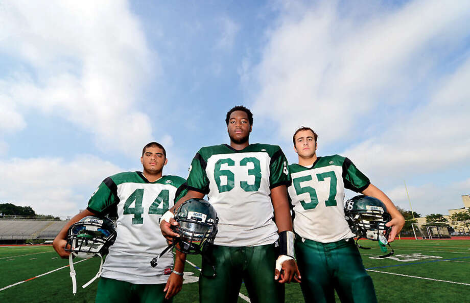 Hour photo / Erik Trautmann Norwalk High School football captains Ricky Mejia, Evan Adams and Billy Passero.