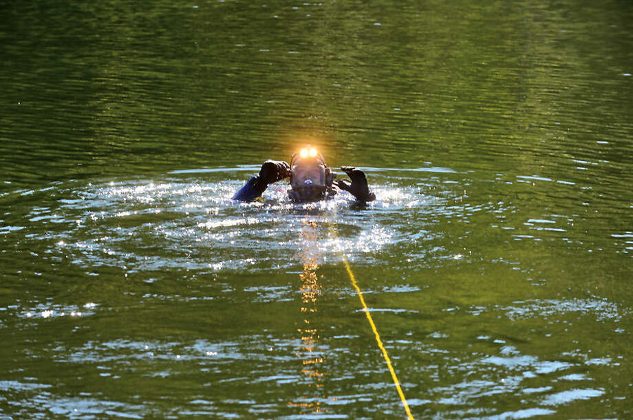 Hour photo / Erik Trautmann Wilton fierfighter Bill Wilson and the Wilton and Westport Police and Fire Departments conduct water rescue training with their dive units Thursday morning in Wilton.