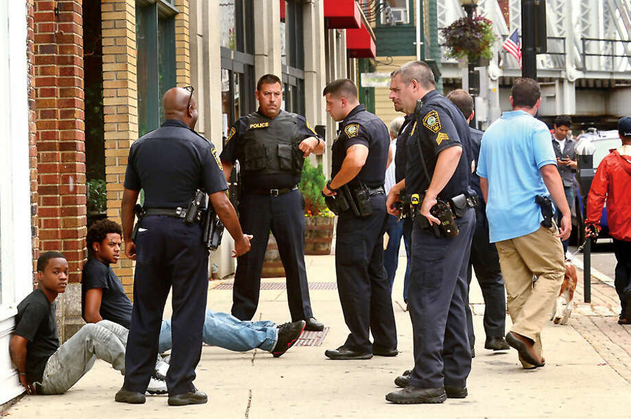 Hour photo / Erik Trautmann Norwalk police investigate a shooting on Ann St and apprehend three suspects on North Main shortly after the incident Wednesday afternoon.