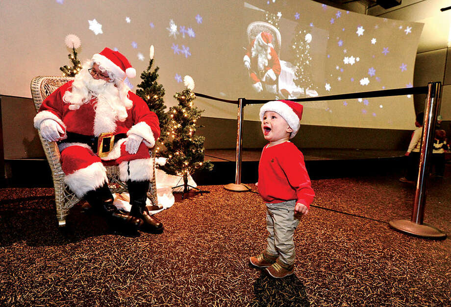 Hour photo / Erik Trautmann 1 year old Nicholas Yeager reacts to encountering another Nicholas played by Stepping Stones educator Jeremy Smith as the North Pole come to Stepping Stones Children's Museum Tuesday afternoon.