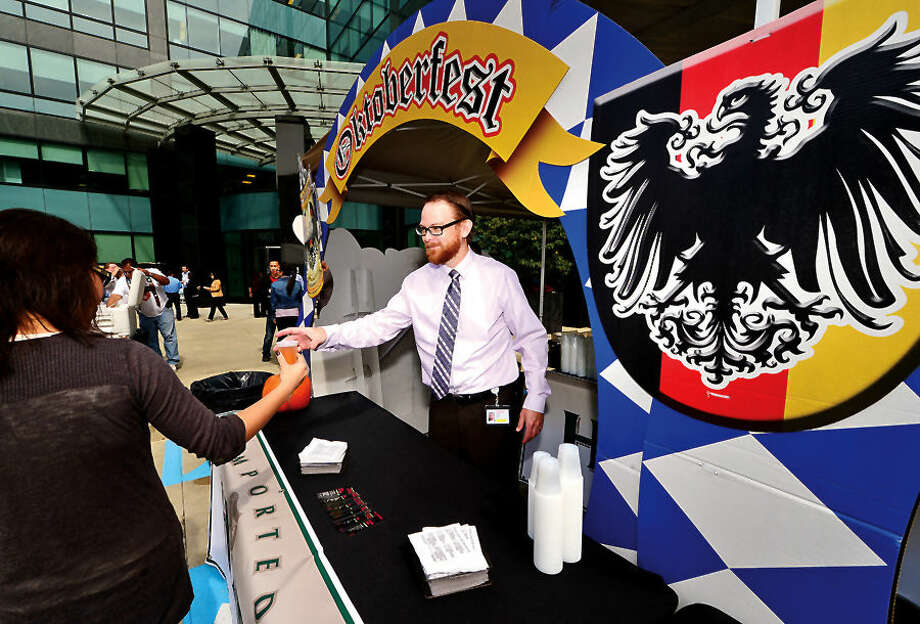 Hour photo / Erik Trautmann Diageo National Beverage Director Patrick Johns hands out beer during the Building and Land Technology's Towers Tenant Appreciation Oktoberfest Picnic Wednesday.