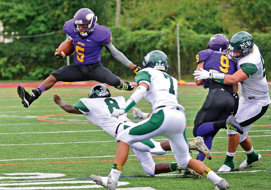 Hour photo / Erik Trautmann Westhill High school's Mehran Dar leaps over Norwalk defenders during their game in Stamford Saturday.