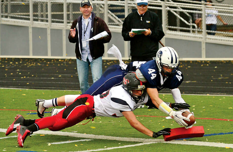 Hour photo / Erik Trautmann Wilton High School Warrior #44 Jack Dexter dives for the touchdown while in the grasp of MUstang #42 Nick Sardone during their game against Fairfield Warde Saturday in Wilton