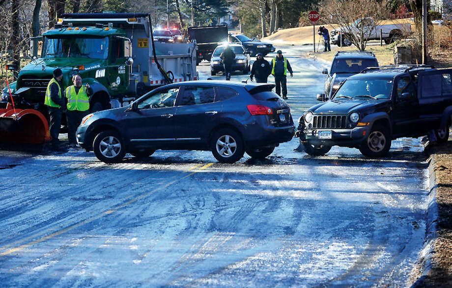 Hour photo / Erik Trautmann A pool water drained from a residence on Westview Lane ice over a trecherous curve on Flax Hill Rd causing a multi vehicle accident that including a DPW plow who was addressing the icing issue Thursday morning