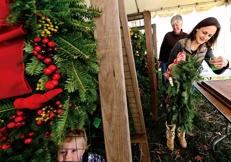 Hour photo / Erik Trautmann Rowayton Garden Club members, including Carey Hahn who was accompanied by her 2 year old son Sebastian, build over 100 wreaths Thursday for their annual Christmas Sale this Saturday at the Rowayton Community Center.