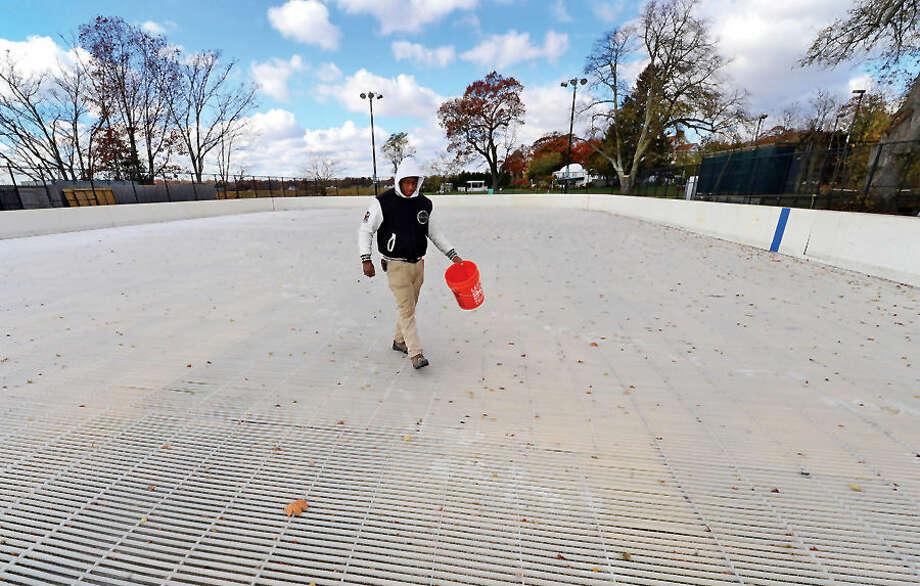 Hour photo / Erik Trautmann Nick Williams helps ready the Westport PAL Ice Rink in Westport for it's seasonal debut next week.
