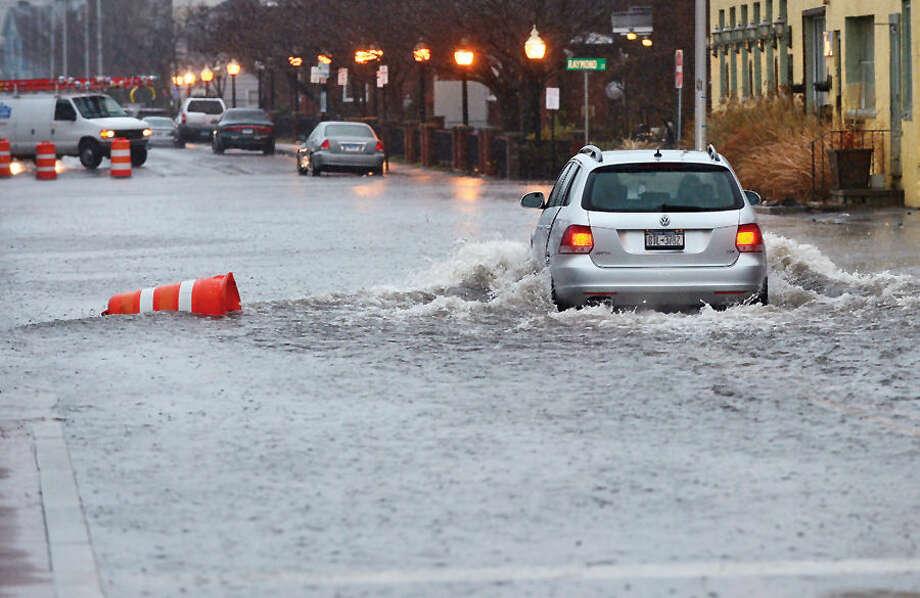 Hour photo / Erik Trautmann Heavy rains and a high tide Tuesday floods Water Street in South Norwalk.