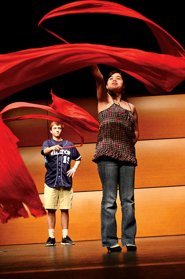 Hour photo / Erik Trautmann 9th grader Ilissa Davison joins members of the Dance China troupe as they perform as part of Wilton High School's annual World Language and Arts Festival Wednesday. The weeklong program features several international events where students will be introduced to different cultures through language lessons, historical background and demonstrations.