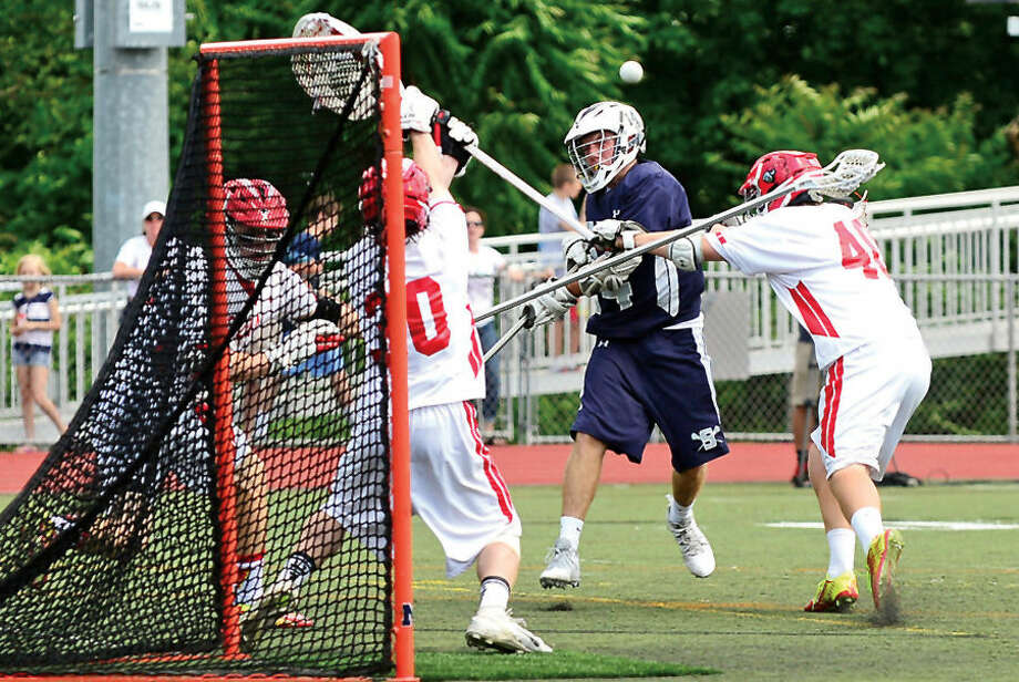 Hour photo / Erik Trautmann Staples # 4 Conor Keenan shoots on goal as they play Greenwich in the boys Class Llacrosse championship game Saturday at Brien MacMahon High School..