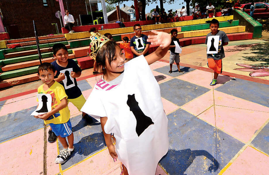 Hour photo / Erik Trautmann Carver Foundation Summer campers including Gisel Aguilar as the Black Queen participate in a game of human chess during the Friends of Ryan Park Summer Camper Awards celebration at the Park Friday afternoon. The Carver Foundation runs summer programs for more than 600 Norwalk children.