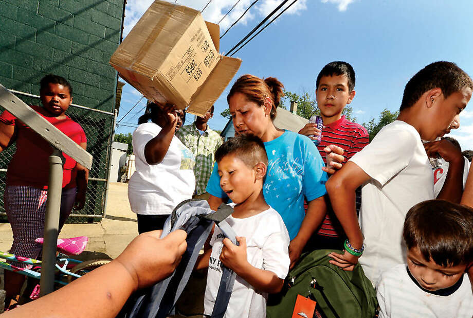 Hour photo / Erik Trautmann John Garcia receives a new back pack donated by the Northeast Community Church during the Bouton St. Back to School Block Party Saturday.