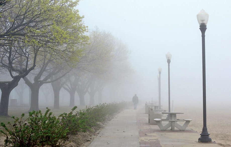 Hour photo / Erik Trautmann A walk walks along a foggy Calf Pasture Beach Tuesday morning.