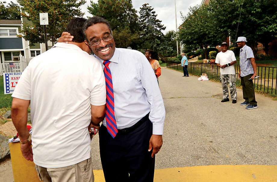 Hour photo / Erik Trautmann State representative Bruce Morris (D-140) greets supporter Raphael Degro during primary voting Tuesday at Columbus Magnet School.
