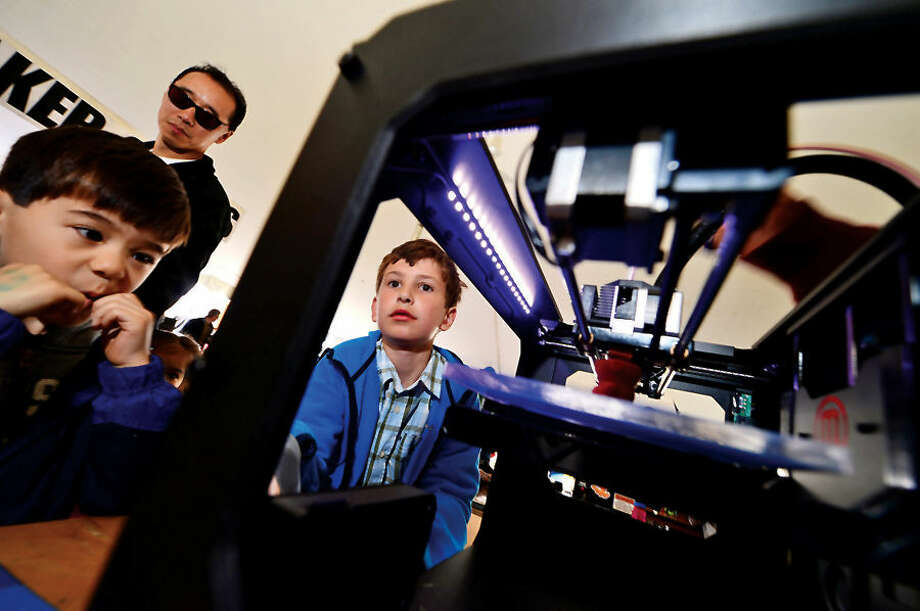 Hour photo / Erik Trautmann Connor Yuan, 5, and Jeffrey Pogue, 9, check out a Maker Bot 3-d printer during the annual Mini Makers Faire at the Jessup Green in Westport