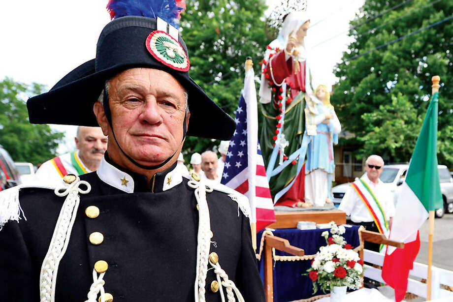 Hour photo / Erik Trautmann members of St. Ann's Club including John Johnson parade to and from St. Thomas Church as part of the annual St. Ann's Feast on Hendrick's Ave this weekend.