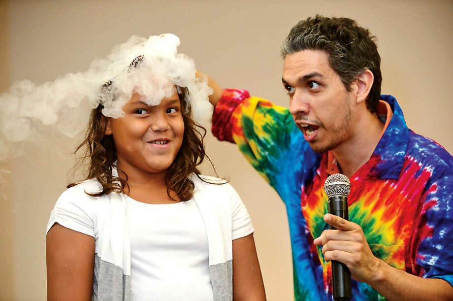 "Hour photo / Erik Trautmann Interactive science storyteller, Justin Maruri, otherwise known as a Scienceteller, and volunteer Camila Santos use dry ice during the presentation of ""Dragons & Dreams!"" at the South Norwalk Branch Public Library Thursday. The Sciencetellers teach science to their audience by telling a lively, interactive and exciting story intertwined with basic science principles."