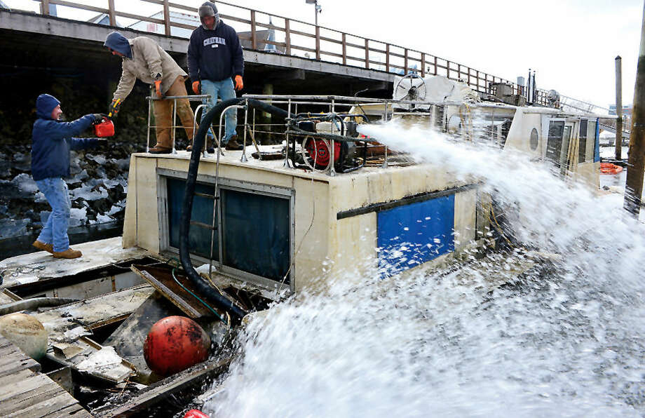 Hour photo / Erik Trautmann Workers with G&C Marine remove a sunken houseboat at Oyster Bend Marina that sunk over the wekend and dumped over 1000 gallons of fuel into the Norwalk River