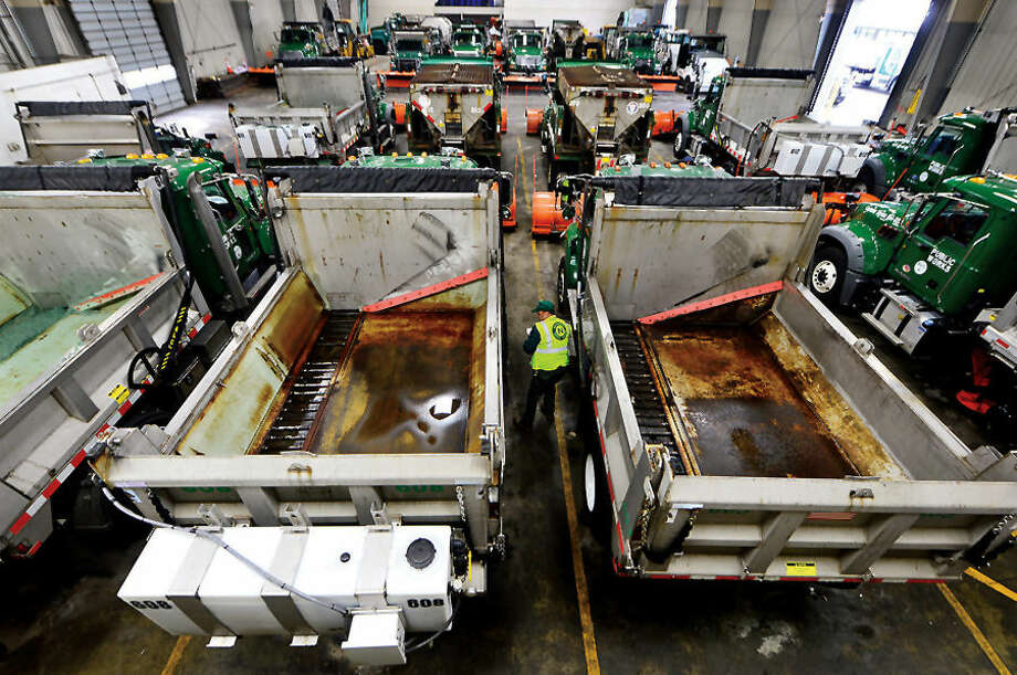 Hour photo / Erik Trautmann DPW employee Donnie Bradley inspects his truck as Department of Public Works officials outline snow-removal technology at press conference at Public Works Center at 15 South Smith St. Wednesday.