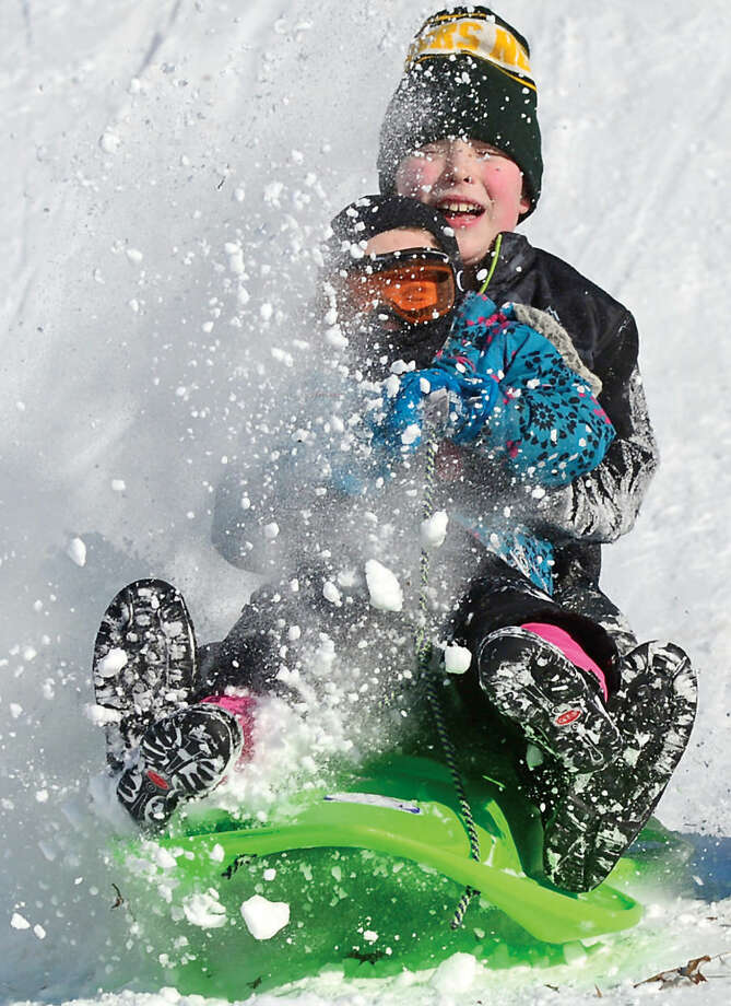 Hour photo / Erik Trautmann Brandon Gilchrist and his sister Kiera, 4, sled at West Rocks School Saturday.