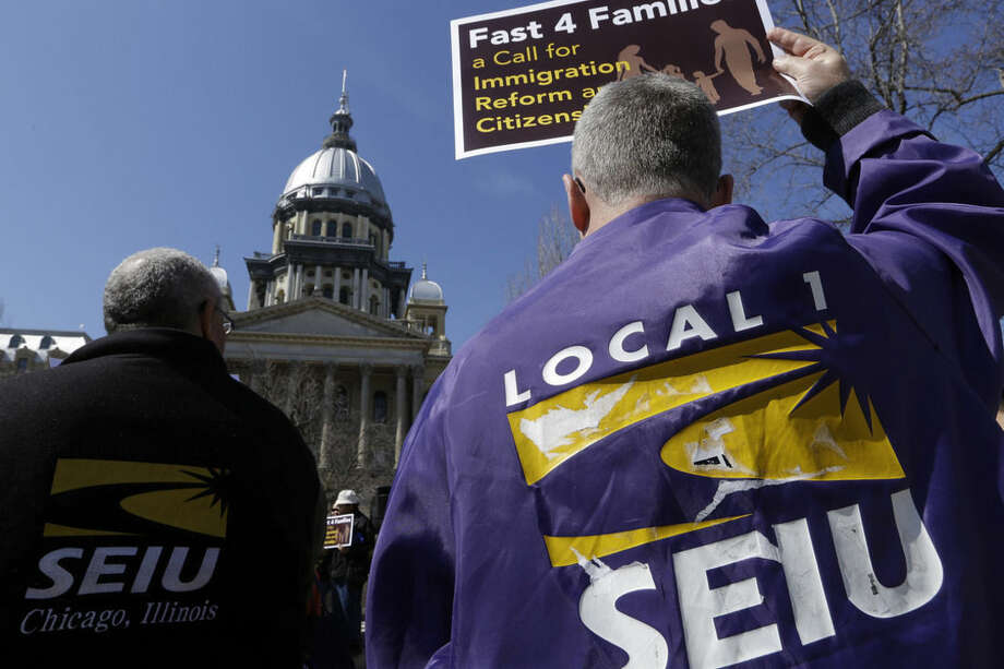 FILE - In this March 20, 2014 file photo, members of the Service Employees International Union, SIEU, rally in front of the Illinois State Capitol in support of Immigration reform in Springfield, Ill. Unions across the U.S. are reaching out to immigrants affected by President Obama's recent executive action in hopes of expanding their dwindling ranks by recruiting millions of workers who entered the U.S. illegally. Labor leaders say the action will give new protection to workers who've been reluctant to join for fear of retaliation. The action curbs deportation and gives work permits to some 4 million immigrants. (AP Photo/Seth Perlman,File)