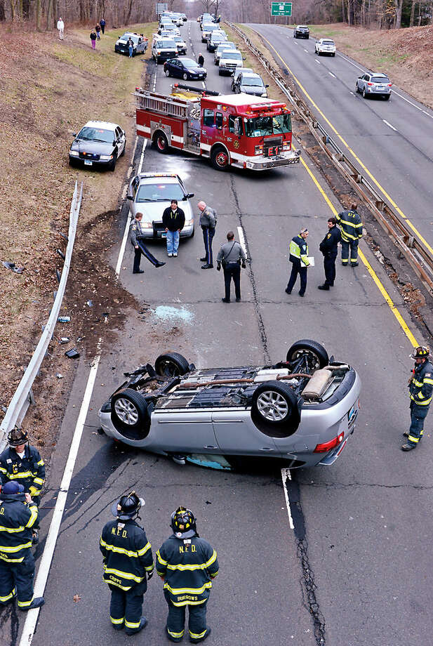 Hour photo / Erik Trautmann CT State police administer a field sobriety test on the driver of a Nissan that rolled over on the Merritt Parkway Northbound between exits 28 and 29 in a single car accident that shut down traffic in both directions.