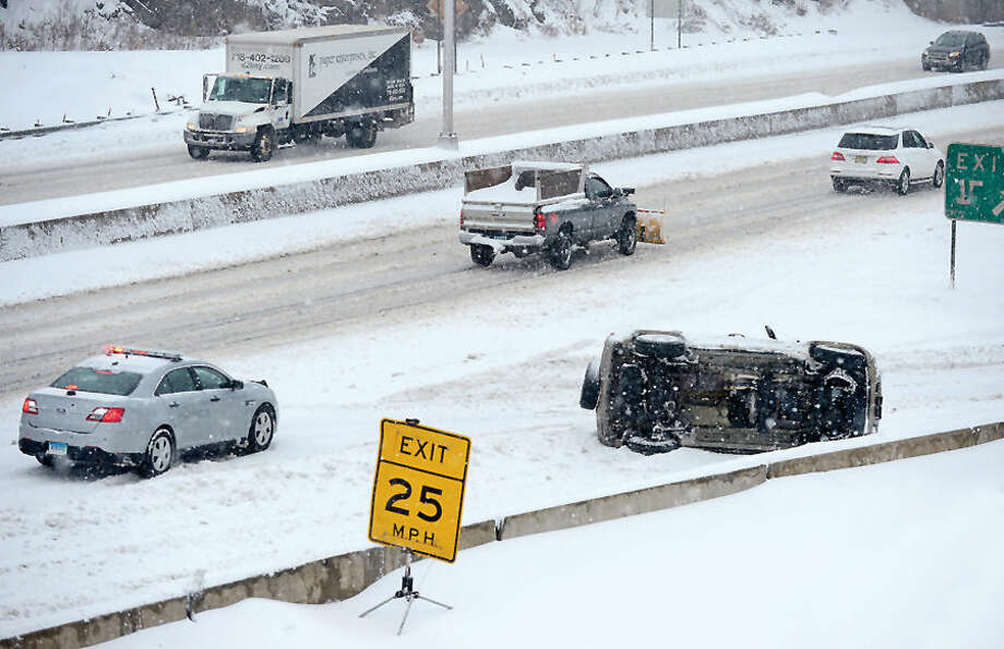 Hour photo / Erik Trautmann A motor vehicle rolled over in a one car accident that blocked the the Exit 15 off ramp on the Northbound side of I-95 during the snowstorm Thursday afternoon.