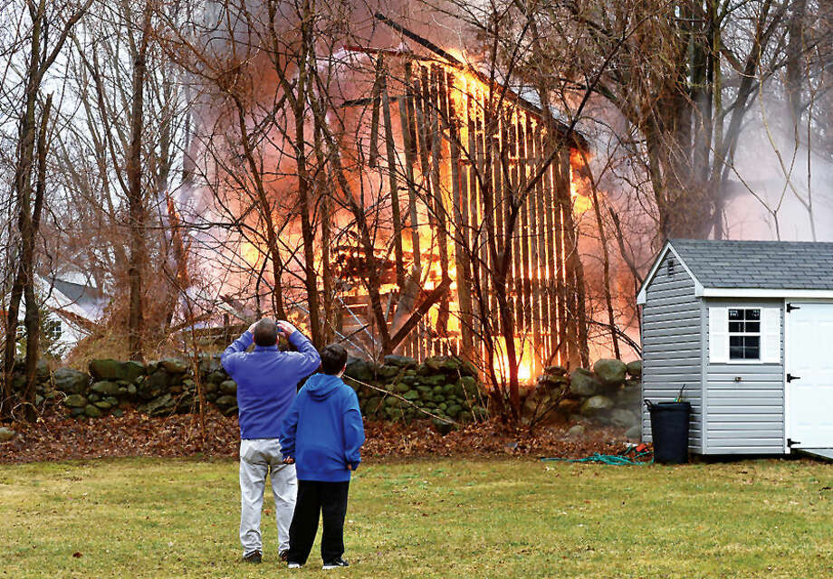 Hour photo / Erik Trautmann Jerry Quinn and his son Connor watch as a barn at 41 Fox Run Rd in Norwalk is destroyed by fire Saturday afternoon.
