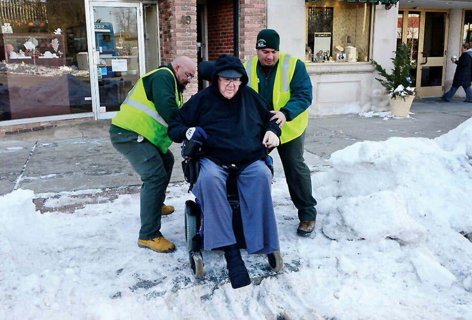 Hour photo / Erik Trautmann DPW workers Mark Re and Adrian Ibarrando help handicapped Norwalk resident John Bennett negotiate a snowy path to the sidewalk while the workers were clearing snow from Wall St Wednesday.