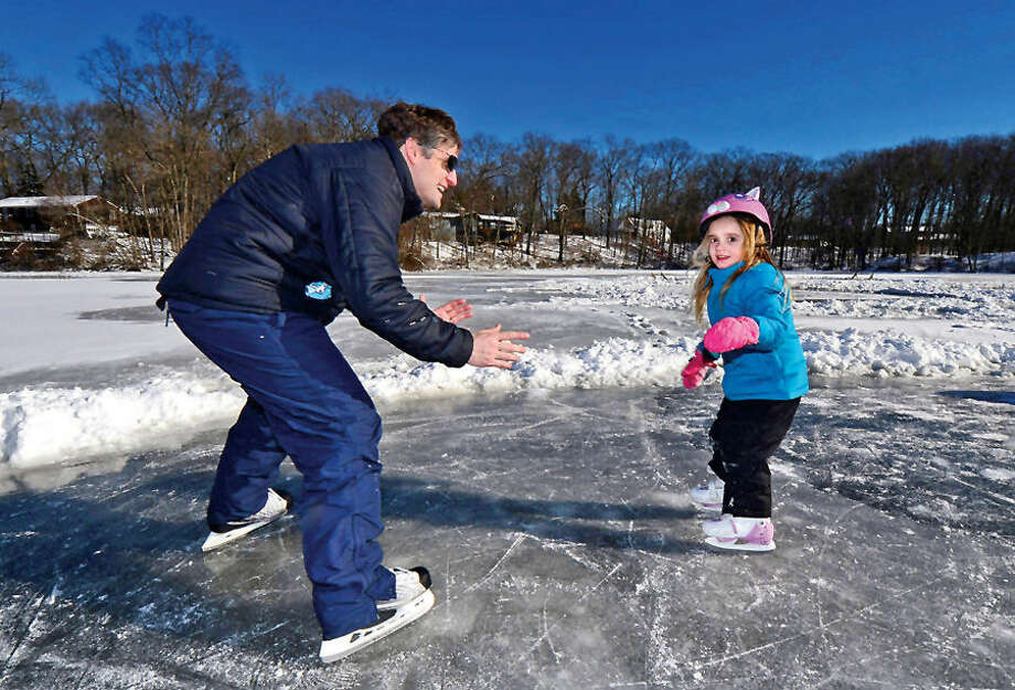 Hour photo / Erik Trautmann Frank Robertson teaches his daughter Ruby, 4, how to skate at Woods Pond Saturday.