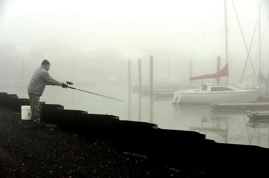 Hour photo / Erik Trautmann Norwalk resident Ingnacio Cervantes casts into Cove Marina during a foggy day Saturday.