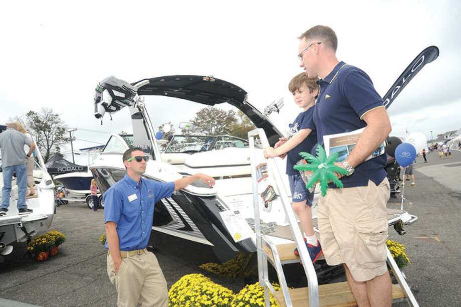 Travis JKeany with Candlewood East Marina speaks with John Turney and his 6 year old son Nathan checking out a Cobalt R3 boat on Sept. 21, 2014 at the Norwalk Boat Show held at Norwalk Cove Marina. Hour photo/Matthew Vinci
