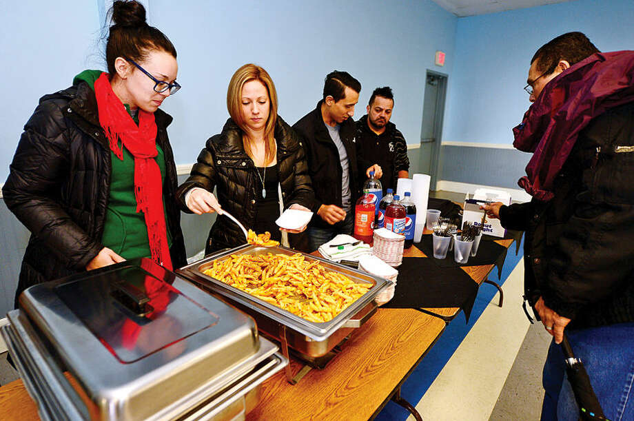 Hour photo / Erik Trautmann Washington Prime staff Nicole Fenton, Samantha Mason, Christian Maldanado and Wilson Suniga serve up baked ziti as the Norwalk Police Department Community Policing Division and Washington Prime restaurant host a Free Christmas Day Luncheon & Coat Drive Thursday at the South Norwalk Community.