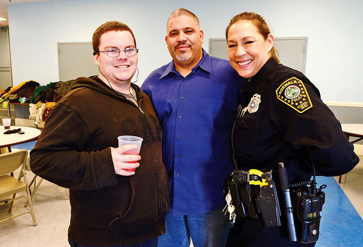 Hour photo / Erik Trautmann Robert Springer pose with Community Police Officers Hector Gonzalez and the Kelly Hollister as the Norwalk Police Department Community Policing Division and Washington Prime restaurant host a Free Christmas Day Luncheon & Coat Drive Thursday at the South Norwalk Community.