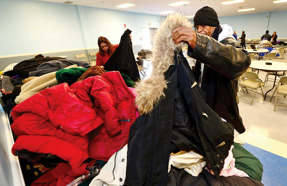 Hour photo / Erik Trautmann Robert Vann sorts through coats asthe Norwalk Police Department Community Policing Division and Washington Prime restaurant host a Free Christmas Day Luncheon & Coat Drive Thursday at the South Norwalk Community.