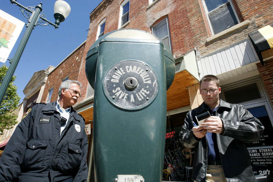 In this May 21, 2008 photo, parking enforcement officer Giovanni Serra, right, watches as Sycamore Police Department intern Justin Keller writes a ticket in downtown Sycamore, Ill. Sycamore is one of the last communities in the country with parking meters that accept pennies. A few other towns have hung onto maybe a dozen or so meters as a reminder of a simpler time. But people who track parking in the United States say they've never heard of another town that has anywhere close to the 316 that are in Sycamore. (AP Photo/Daily Chronicle, Eric Sumberg) MANDATORY CREDIT
