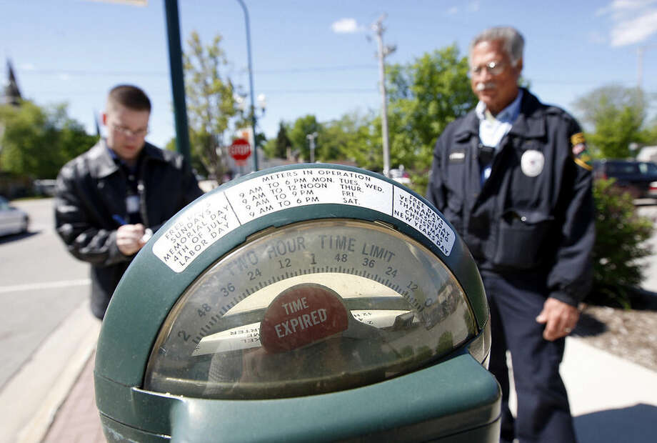 In this May 21, 2008 photo, parking enforcement officer Giovanni Serra, left, watches as Sycamore Police Department intern Justin Keller writes a ticket in downtown Sycamore, Ill. Sycamore is one of the last communities in the country with parking meters that accept pennies. A few other towns have hung onto maybe a dozen or so meters as a reminder of a simpler time. But people who track parking in the United States say they've never heard of another town that has anywhere close to the 316 that are in Sycamore. (AP Photo/Daily Chronicle, Eric Sumberg) MANDATORY CREDIT