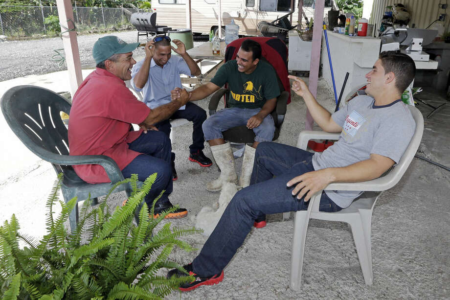 ADVANCE FOR SATURDAY DEC. 27, 2014 In this photo taken Saturday, Sept. 28, 2014, from left, Antonio Cardenas, Yanier Martinez Diaz, Wilfredo Suarez and Jose Fuente Lastre, in Miami, during a gathering of rafters who came together risking their lives in the 110-mile journey at sea, in Miami. (AP Photo/Alan Diaz)