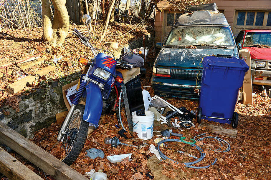 Hour photo / Erik Trautmann Debris and unused vehicles in the driveway at 10 Richmond Hill Rd. There are sixty Norwalk properties cited under city's blight ordinance. Members of Common Council's Ordinance Committee are discussing strengthening the ordinance.