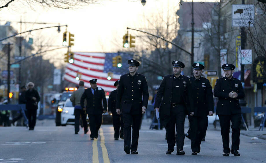 New York City police officers walk toward Christ Tabernacle Church before funeral services for officer Rafael Ramos at in the Glendale section of Queens, Saturday, Dec. 27, 2014, in New York. Ramos and his partner, officer Wenjian Liu, were killed Dec. 20 as they sat in their patrol car on a Brooklyn street. The shooter, Ismaaiyl Brinsley, later killed himself. (AP Photo/Julio Cortez)