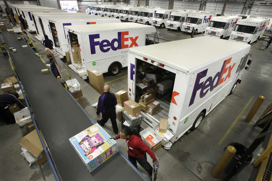 FILE - In this Dec. 15, 2014 file photo, FedEx employees pull boxes from a conveyor belt and fill their trucks for deliveries at a FedEx sorting facility in the Bronx borough of New York. After FedEx and UPS failed to deliver some presents in time for Christmas last year, the two package carriers seem to have improved their performance this holiday season. But shipments from retailers weren't without hiccups. (AP Photo/Mark Lennihan, File)