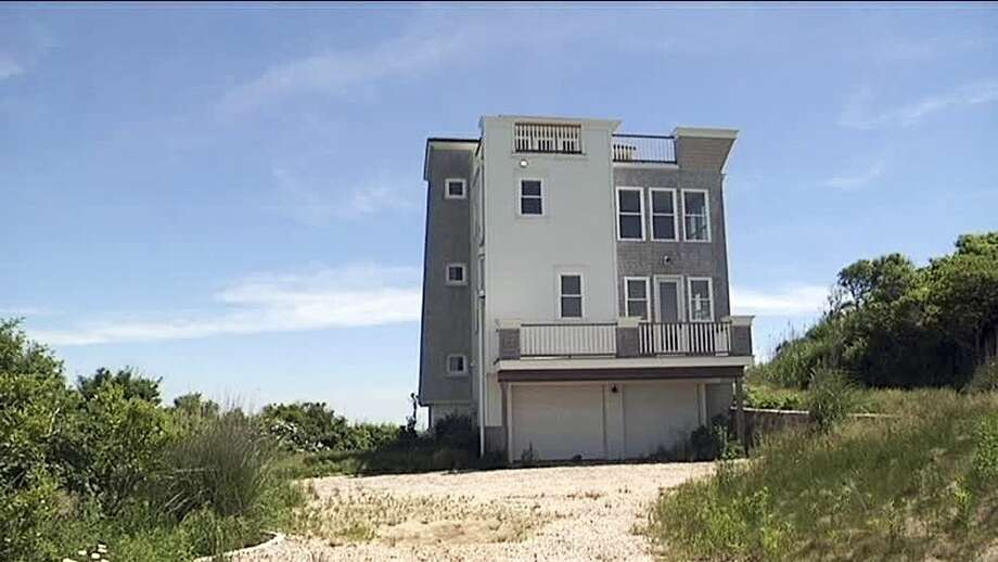 FOR RELEASE FRIDAY, DECEMBER 26, 2014, AT 12:01 - FILE-- This June 16, 2014 file photo shows a $1.8 million waterfront house, that a developer mistakenly built on park land, in Narragansett, R.I., and which the Rhode Island Supreme Court ordered to be removed. Construction began in 2009, but the developer didn't discover the error until 2011 when attempting to sell it. A foundation had been set up to preserve the property as a park in perpetuity, and the developer was told the land was not for sale. (AP Photo/WJAR-TV, File)
