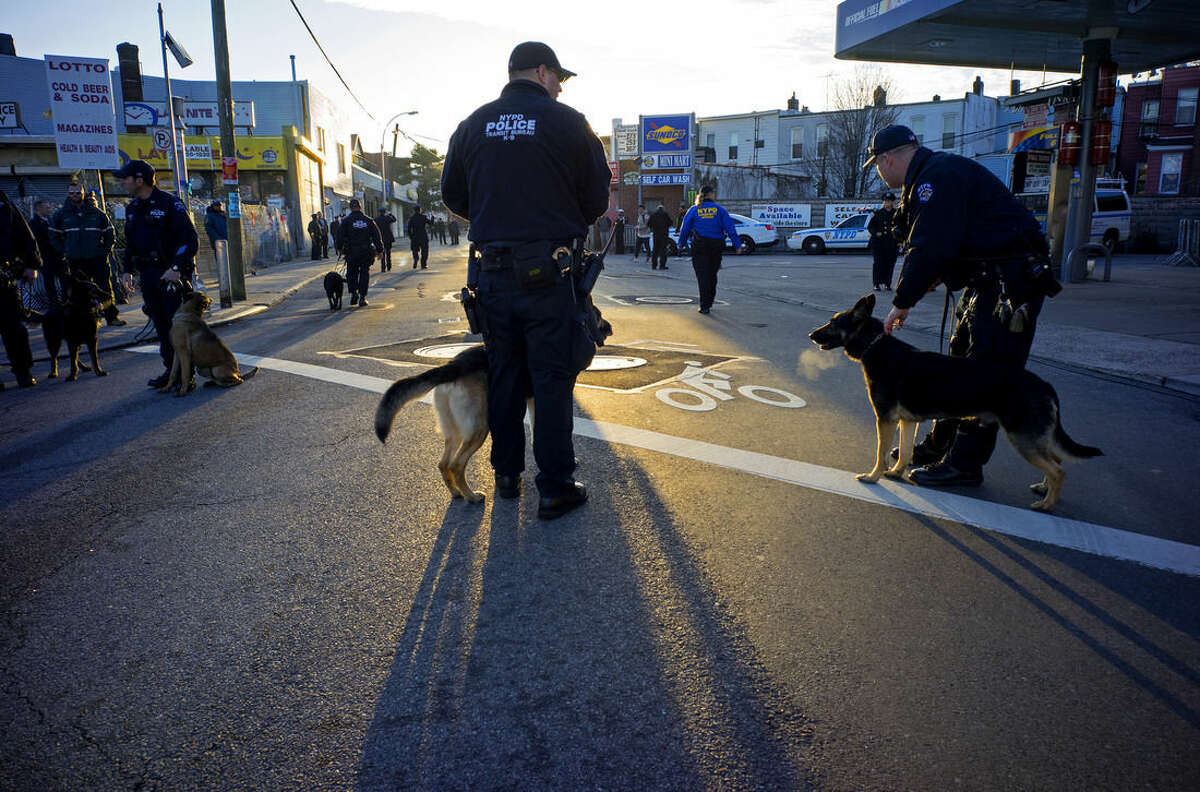 Police officers and their dogs assemble before the funeral of New York City police officer Rafael Ramos at Christ Tabernacle Church in the Glendale section of Queens, where he was a member, Saturday, Dec. 27, 2014, in New York. Ramos and his partner, officer Wenjian Liu, were killed Dec. 20 as they sat in their patrol car on a Brooklyn street. The shooter, Ismaaiyl Brinsley, later killed himself. (AP Photo/Craig Ruttle)
